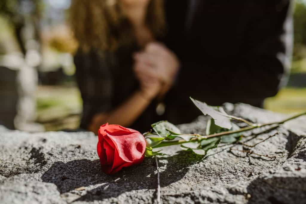 A couple grieving by a grave. A closeup on a rose on top of the headstone.