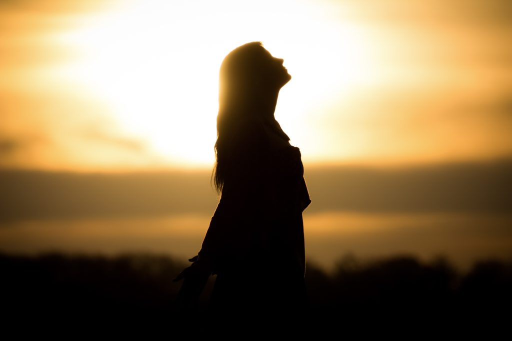 Silhouette of a woman looking up in front of sunset.