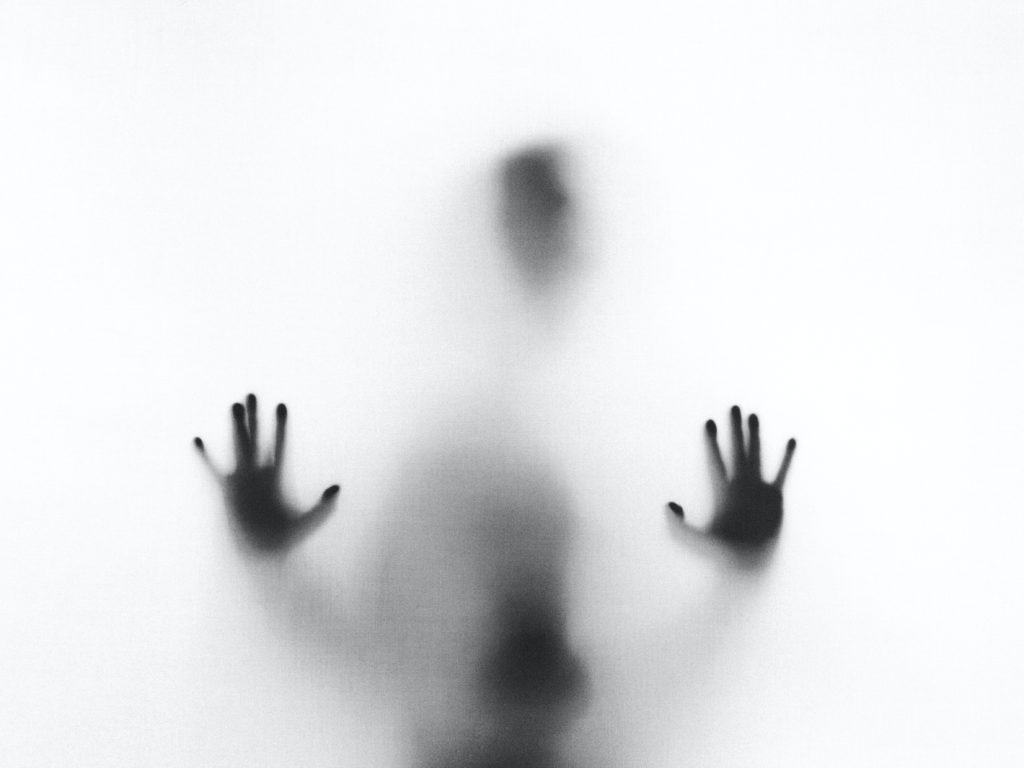 A dark figure on the other side of frosted glass with their hands on the glass.
