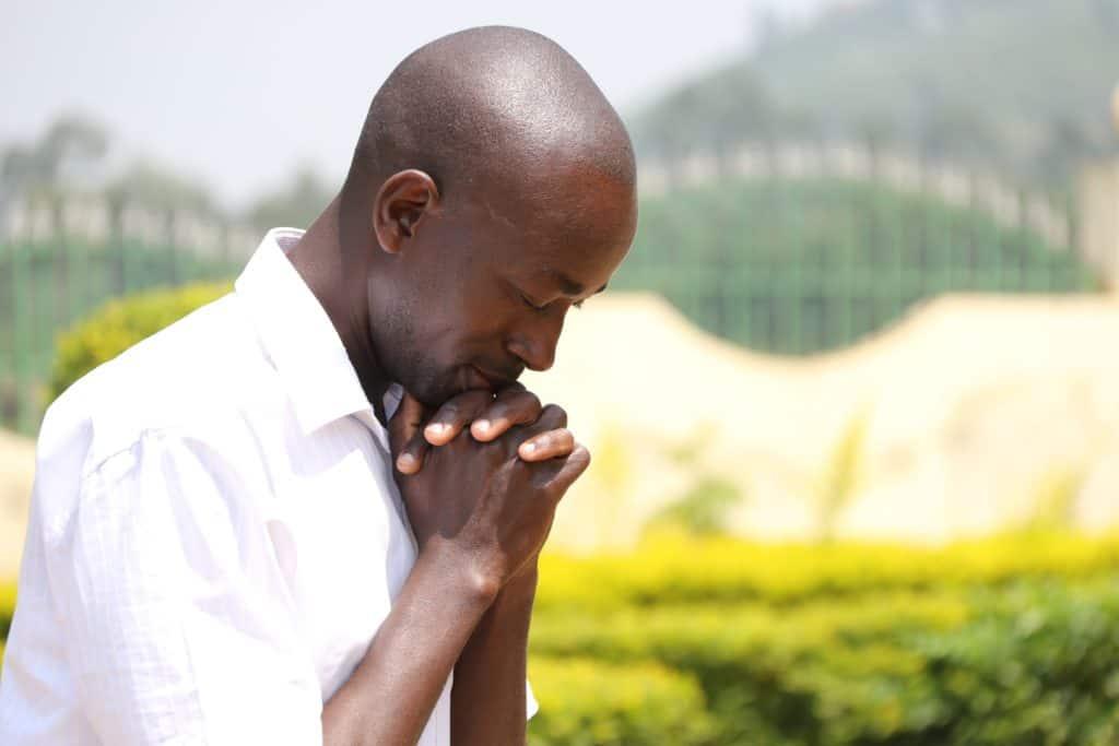 A man praying outside.
