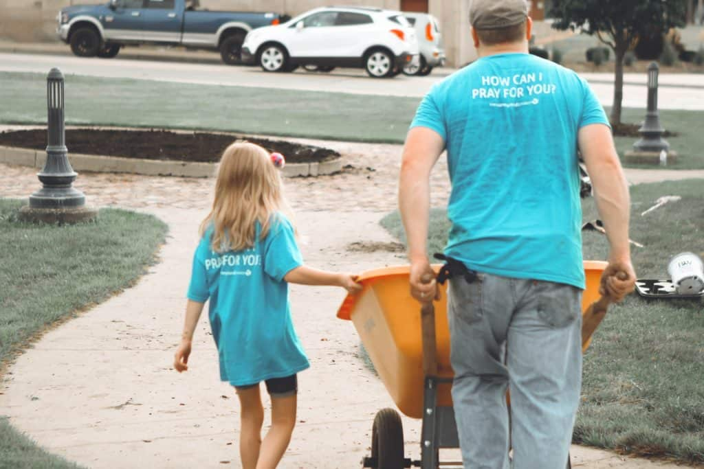 A man and a young girl volunteering wearing shirts that say 'how can I pray for you?'