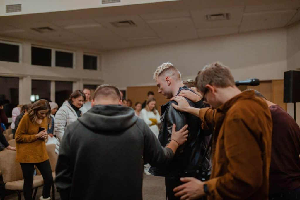 A group of people at a church praying for someone with their hands on him.