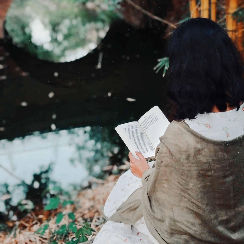 A woman reading in a garden.