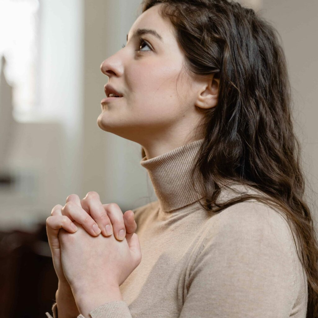 A young woman with her hands folded in prayer and looking up.