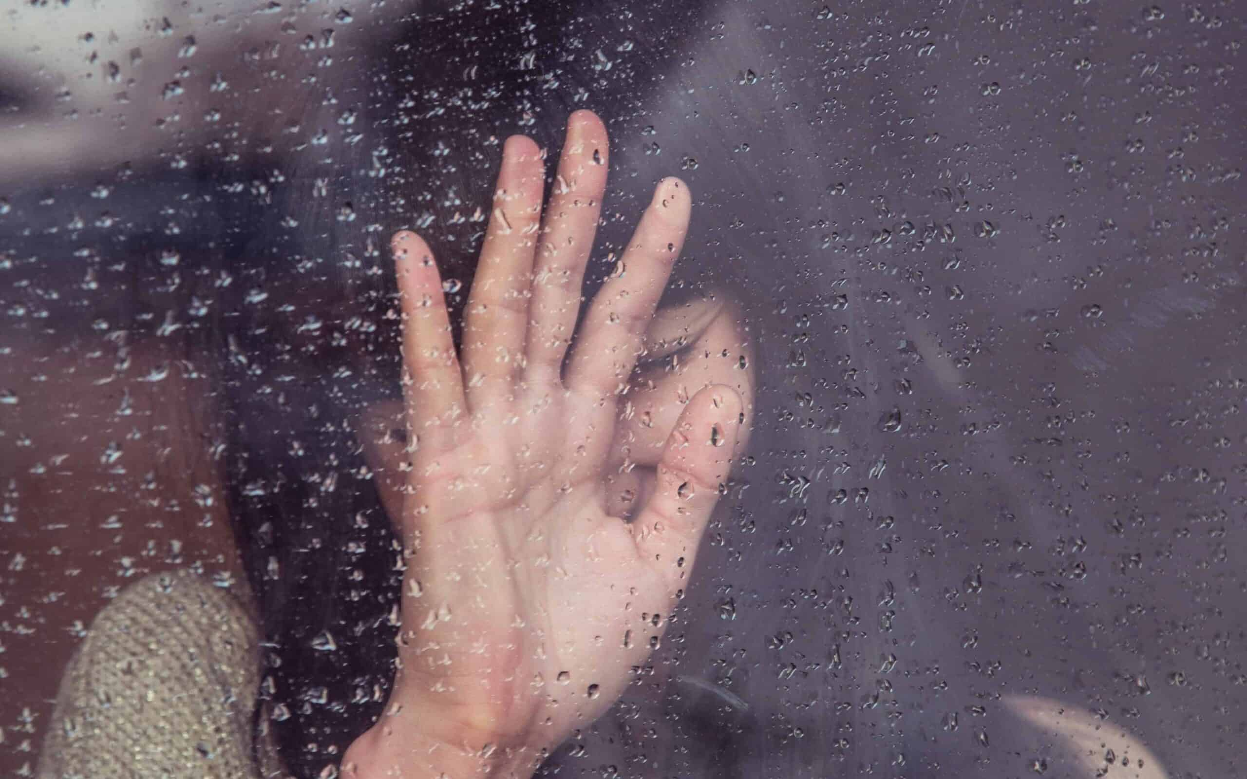 A sad, crying woman standing at a window with raindrops on it.
