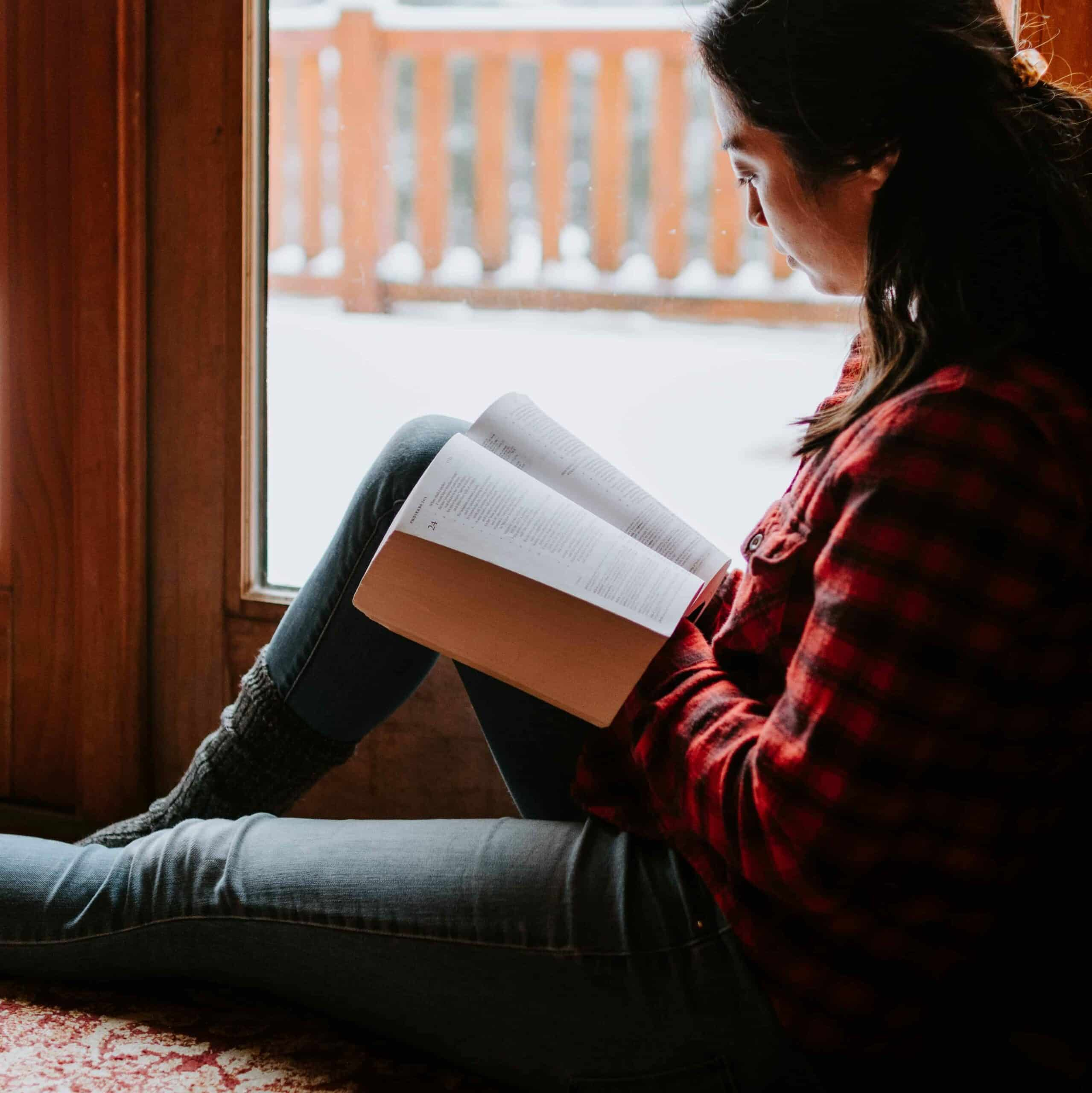 A woman reading the Bible by a window.